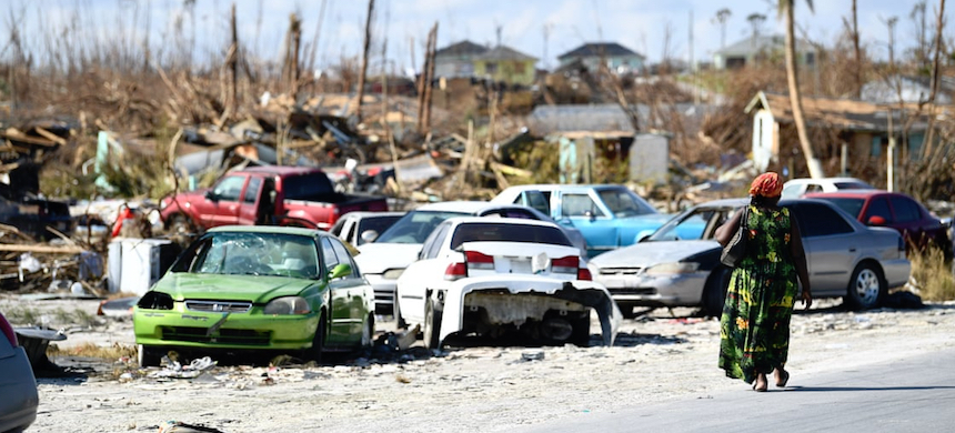 A woman walks by destroyed cars in the Mudd neighborhood in Marsh Harbour, Great Abaco, on 7 September 2019, in the aftermath of Hurricane Dorian. (photo: Brendan Smialowski/AFP/Getty Images)