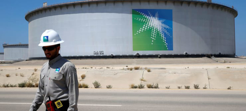 An Aramco employee walks near an oil tank at Saudi Aramco's Ras Tanura oil refinery and oil terminal in Saudi Arabia. (photo: Ahmed Jadallah/Reuters)