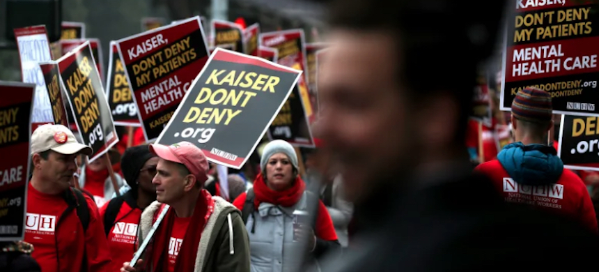 Kaiser Permanente mental health workers carry signs as they march. (photo: Getty Images)