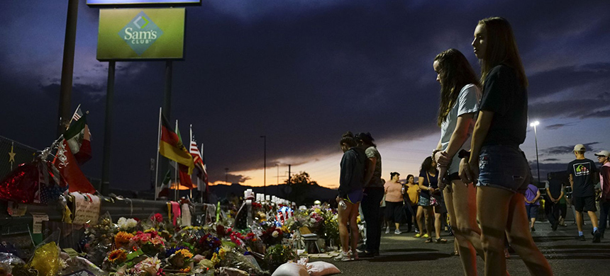 People gather at a makeshift memorial honoring victims outside Walmart in El Paso, Texas. 22 people were killed in the Walmart during a mass shooting on August 3, 2019. (photo: Sandy Huffaker/Getty Images)