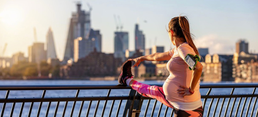 A pregnant woman works out in front of the skyline of London. (photo: Getty)