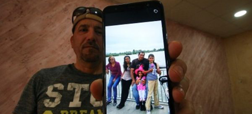 Hani al-Bazoni, who was deported from the U.S. to Iraq under Donald Trump's strengthened immigration enforcement, shows a picture of his family. (photo: Reuters)