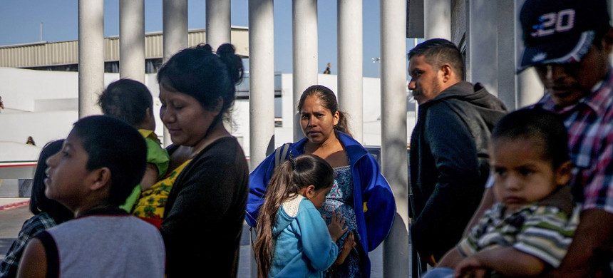 Migrants from Honduras wait in line at the Mexico-United States border crossing in Tijuana, Mexico, on Sept. 12, 2019. (photo: Sandy Huffaker/Getty)