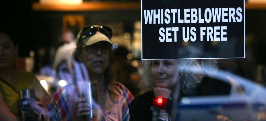 A woman holds a sign about whistleblowers in a cafe near U.S. president Donald Trump's motorcade as he attends a campaign fundraiser nearby in New York, U.S., September 26, 2019. (photo: Jonathan Ernst/Reuters)