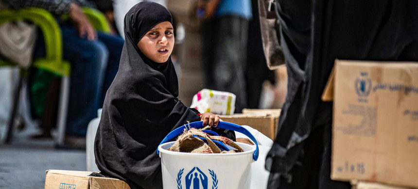 A girl sits next to packages of humanitarian aid at a camp for displaced people in northeastern Syria on July 22, 2019, as people collect UN-provided humanitarian aid packages. (photo: Delil Souleiman/Getty)