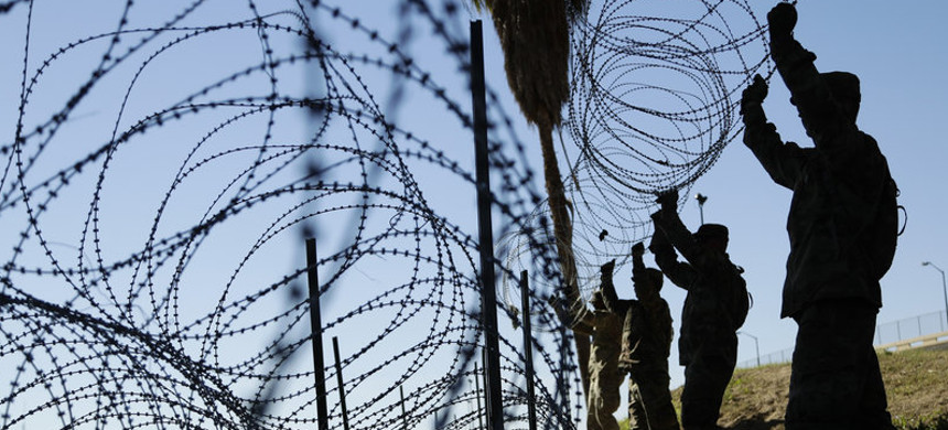 Members of the U.S. military install multiple tiers of concertina wire along the banks of the Rio Grande near the Juarez-Lincoln Bridge at the U.S.-Mexico border in Laredo, Texas, in November. (photo: Eric Gay/AP)