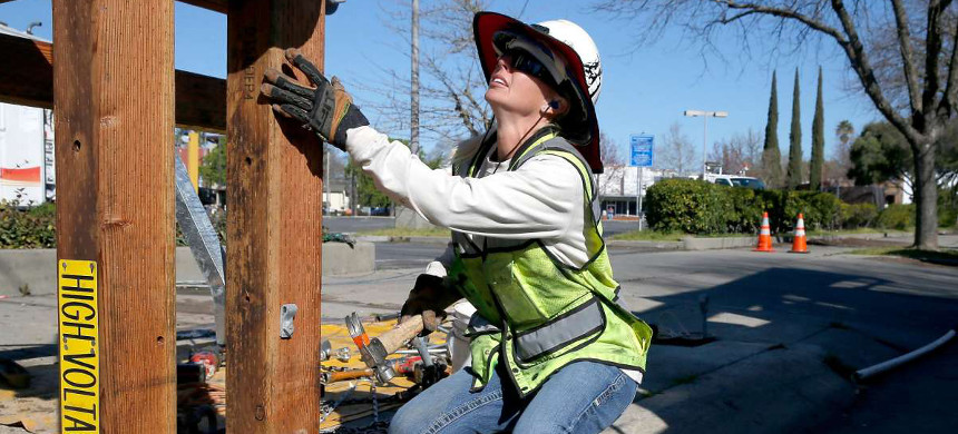 Sacramento Municipal Utility District worker Lindsey Martinez prepares a utility pole for installation. (photo: Paul Chinn/San Francisco Chronicle)