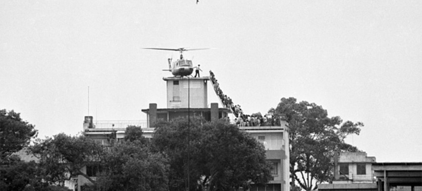 Evacuation of Saigon. A CIA employee (probably O.B. Harnage) helps Vietnamese evacuees onto an Air America helicopter from the top of 22 Gia Long Street, a half mile from the U.S. Embassy. (photo: Getty Images)
