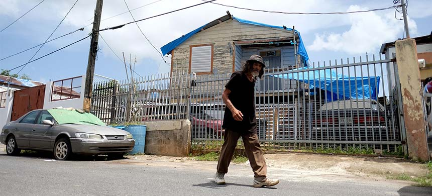 A man walks by a house with the blue tarp that was used to protect the roof damaged by Hurricane Maria in San Juan, Puerto Rico, on Sept. 18, 2019. (photo: Ricardo Arduengo/AFP/Getty Images)