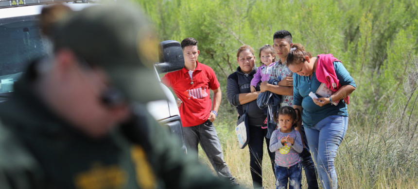 Central American asylum seekers wait as U.S. Border Patrol agents take groups of them into custody. (photo: John Moore/Getty)