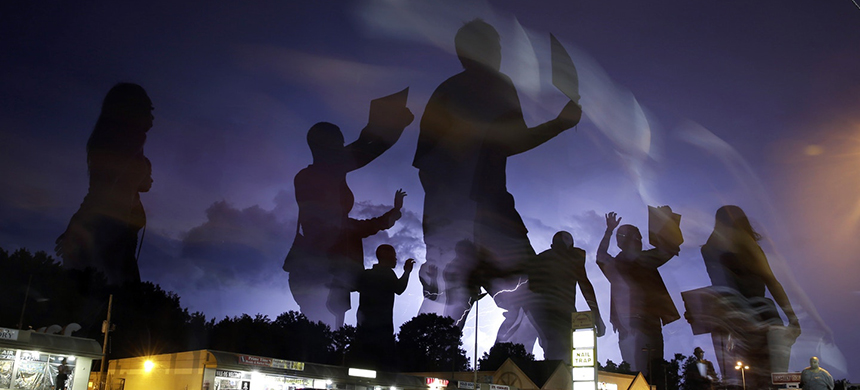 Protesters march in the street as lightning flashes in the distance in Ferguson, Mo., on Aug. 20, 2014. (photo: Jeff Roberson/AP)