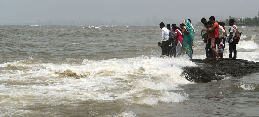 A group of people stand near the coast in Mumbai, India. (photo: Getty)