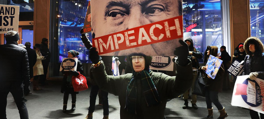 A protester holds a sign calling for Donald Trump's impeachment. (photo: Spencer Platt/Getty)