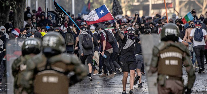 Demonstrators clash with riot police during protests against the government economic policies, in the surroundings of La Moneda presidential palace in Santiago, Chile on Oct. 29, 2019. (photo: Pedro Ugarte/Getty)
