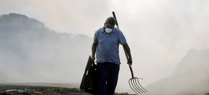 Man attempts work on his property as fires roar nearby. (photo: Marcio Jose Sanchez/AP)