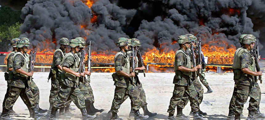 Mexican soldiers walk next to the site of the incineration of 23.5 tons of cocaine in Manzanillo in 2007, a week after the Mexican and US governments announced a joint security plan that included a Mexican pledge to step up the fight against organized crime, especially drug trafficking. (photo: Alfredo Estrella/AFP/Getty Images)
