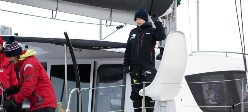 Swedish climate activist Greta Thunberg waves aboard the catamaran La Vagabonde as she sets sail for Europe from Hampton, Va., on Wednesday. (photo: Nicholas Kamm/Getty)