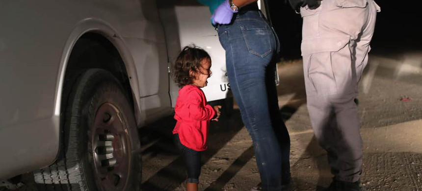 A two-year-old Honduran asylum seeker cries as her mother is searched and detained near the U.S.-Mexico border. (photo: John Moore/Getty)
