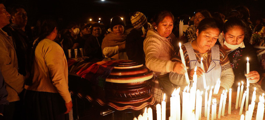 Mourners light candles around coffins of backers of former President Evo Morales that died during clashes with security forces in Sacaba, Bolivia, Friday, Nov. 15, 2019. (photo: Juan Karita/AP)
