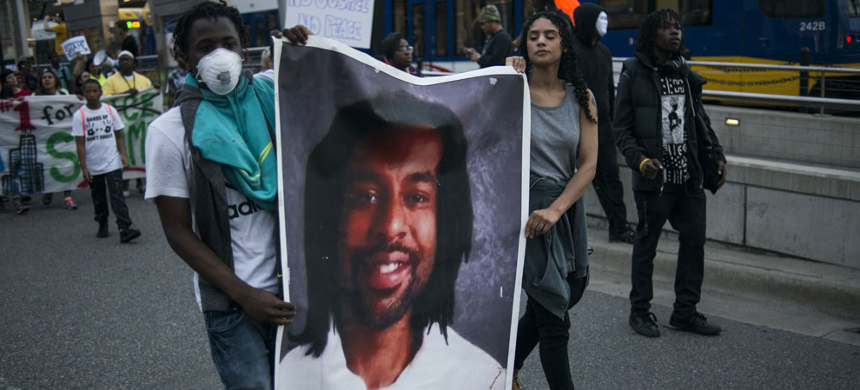 Protesters carry a portrait of Philando Castile on June 16, 2017, in St. Paul, Minnesota. (photo: AFP)