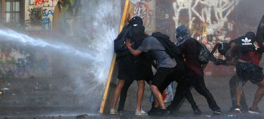 Demonstrators take cover from water fired by a riot police truck during a protest against President Sebastian Piñera on November 19 in Santiago, Chile. (photo: Marcelo Hernandez/Getty Images)