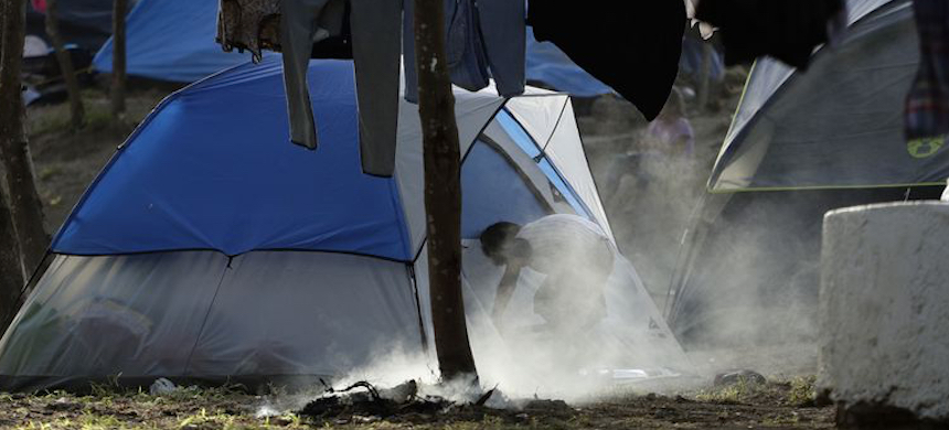 Many migrants seeking asylum and waiting for their U.S. court dates are living in a refu­gee camp, shown early this month, in Matamoros, Mexico. (photo: Eric Gay/AP)