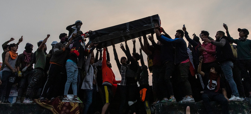 Friends and family members raised the coffin of 16-year-old Hussein Abid, who was killed by Iraqi security forces on Thursday. (photo: Ivor Prickett/NYT)