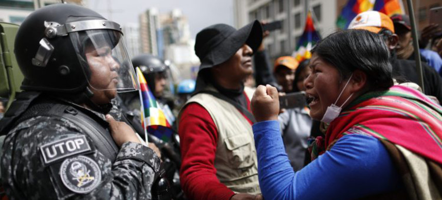 An Evo Morales supporter confronts Bolivian police in La Paz. (photo: Natacha Pisarenko/AP)