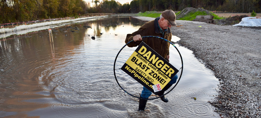 Tom Clark stands in a flooded construction site holding a hula hoop that is 36 inches in diameter - the width the Atlantic Coast Pipeline is slated to be in North Carolina. (photo: Lyndsey Gilpin/Grist)