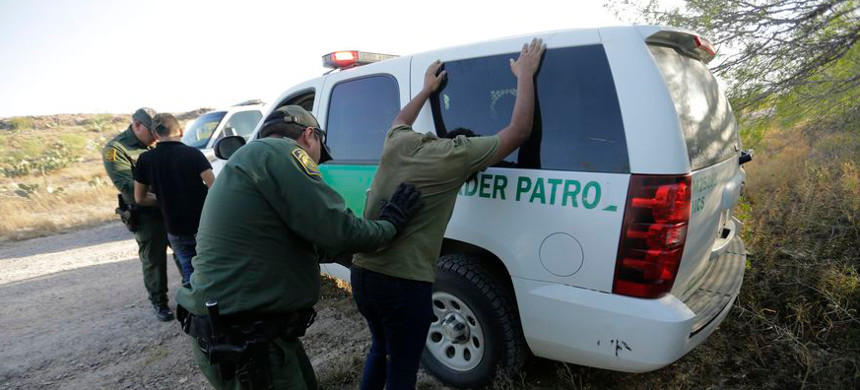 In this Wednesday, Nov. 6, 2019 photo, Border Patrol agents stop two men thought to have entered the country illegally, near McAllen, Texas, along the U.S.-Mexico border. (photo: Eric Gay/AP)
