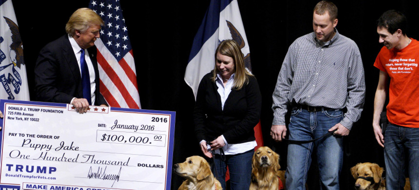 US Republican presidential candidate Donald Trump presents check from Trump foundation to Puppy Jake Foundation. (photo: Rick Wilking/Reuters)