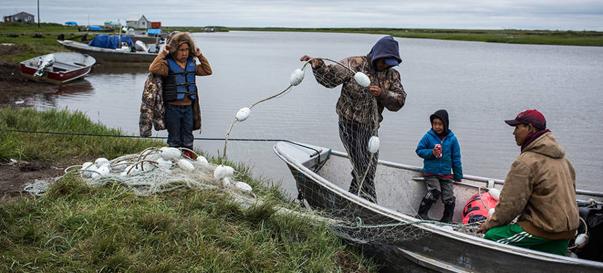 Yupik men prepare a boat to fish for salmon on the Bering Sea. (photo: Andrew Burton/Getty)