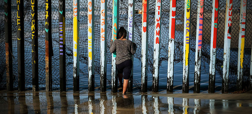 A girl from Salvador looks through the US-Mexico border fence in Playas de Tijuana, Baja California State, Mexico, on December 29, 2018. (photo: Guillermo Arias/AFP/Getty Images)