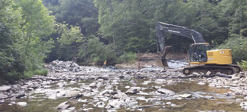Heavy equipment sits on the edge of a rocky stream bank as part of U.S. Bureau of Land Management-Forest Service reclamation efforts for abandoned oil and gas wells in the eastern U.S. (photo: Bureau of Land Management)