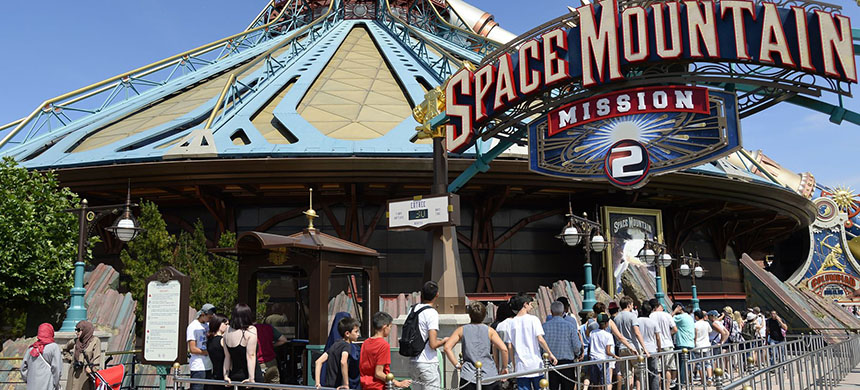 People stand in line at the entrance to the Space Mountain at Disneyland Paris in Marne-la-Vallee in August 2015. French workers, unlike Americans, have guaranteed time off. (photo: Bertrand Guay/AFP/Getty Images)