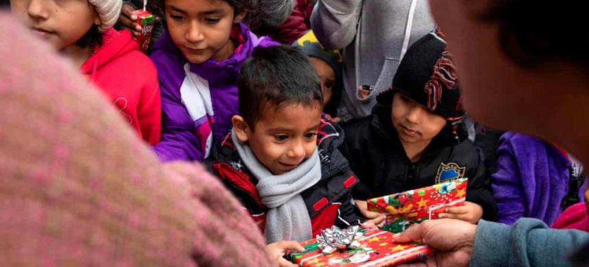 Migrant children receive Christmas gifts from as they wait for visas from U.S. migration authorities outside El Chaparral port of entry in Tijuana. (photo: Eduardo Jaramillo Castro/AFP/Getty Images)