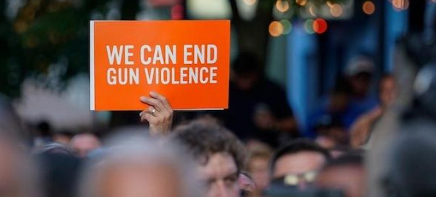 A vigil attendee holds a sign at the scene of a mass shooting in Dayton, Ohio, U.S., August 4, 2019. (photo: Reuters)