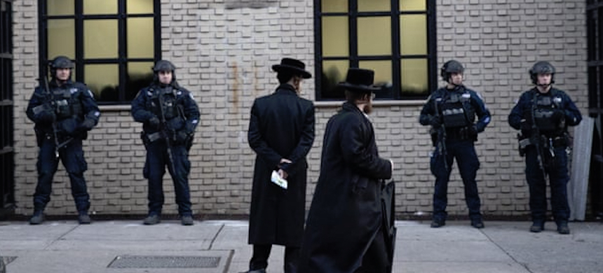Orthodox Jewish men pass police guarding a Brooklyn synagogue prior to a funeral for a victim of the shooting inside a Jewish grocery, 11 December. (photo: Mark Lennihan/AP)