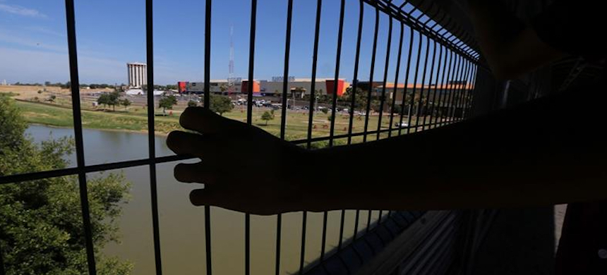 Migrant looking over the Rio Grande river on International Bridge 1 Las Americas, a legal port of entry which connects Laredo, Texas, in the U.S. with Nuevo Laredo, Mexico. (photo: Marco Ugarte/AP)
