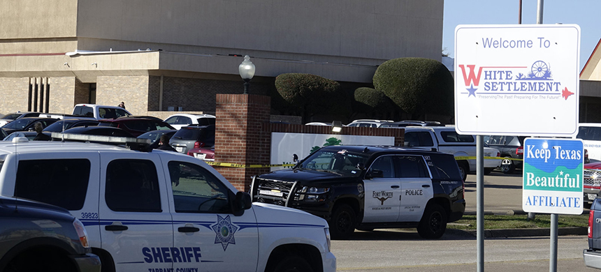 Law enforcement vehicles are seen parked outside West Freeway Church of Christ as authorities continue to investigate a fatal shooting at the church on Sunday, in White Settlement, Texas. (photo: David Kent/AP)