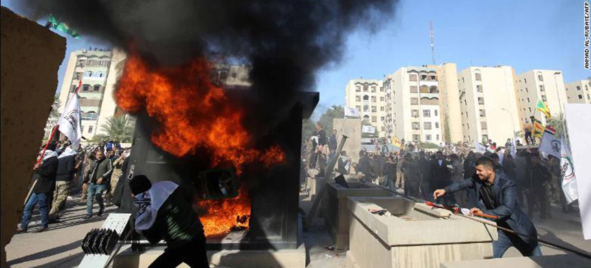 Iraqi protesters set a sentry box ablaze in front of the US embassy in Baghdad on Tuesday. (photo: CNN)