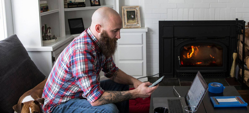 With Frosting the dog keeping him company, Kristofer Goldsmith checks messages from a Facebook scammer who contacted him impersonating a fellow veteran. (photo: Holly Pickett/Buzzfeed News)
