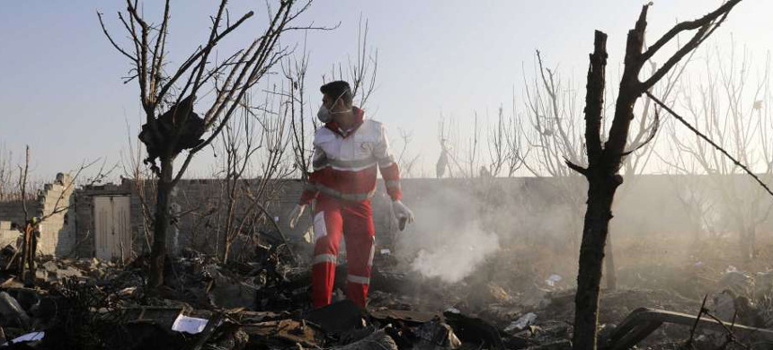 A rescue worker searches the scene where an Ukrainian plane crashed in Shahedshahr, southwest of the capital Tehran, Iran, Wednesday, Jan. 8, 2020. A Ukrainian airplane carrying 176 people crashed on Wednesday shortly after takeoff from Tehran's main airport, killing all onboard. (photo: Ebrahim Noroozi/AP)