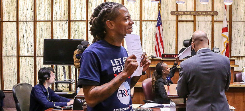 Michael Monfluery, 38, who has never been eligible to vote, holds a paper restoring his right to vote during a special court hearing on Nov. 8, 2019, in Miami. (photo: Zak Bennett/AFP)