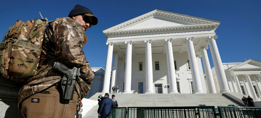 A gun rights activist carries his handgun in a hip holster outside the Virginia state capitol building as the general assembly prepares to convene in Richmond, on 8 January. (photo: Jonathan Drake/Reuters)
