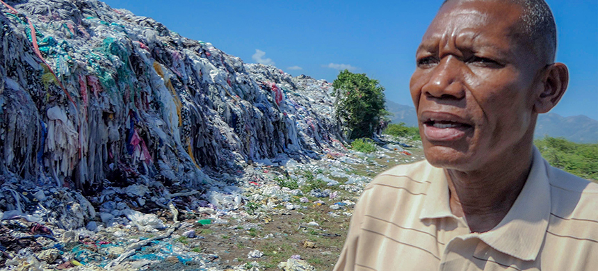 'There was no garbage here before,' environmental activist Milostène Castin says, gesturing at a mountain of trash produced by the garment manufacturing center in Caracol, Haiti. (photo: Jeremy Dupin/In These Times)
