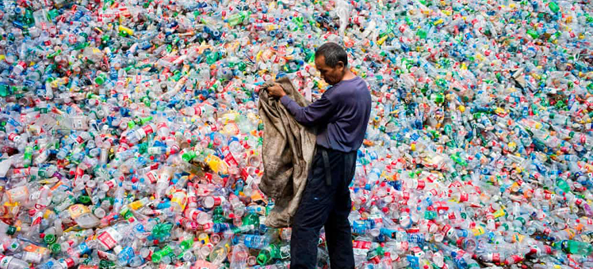 A Chinese labourer sorting out plastic bottles on the outskirt of Beijing. (photo: Fred Dufour/AFP/Getty Images)
