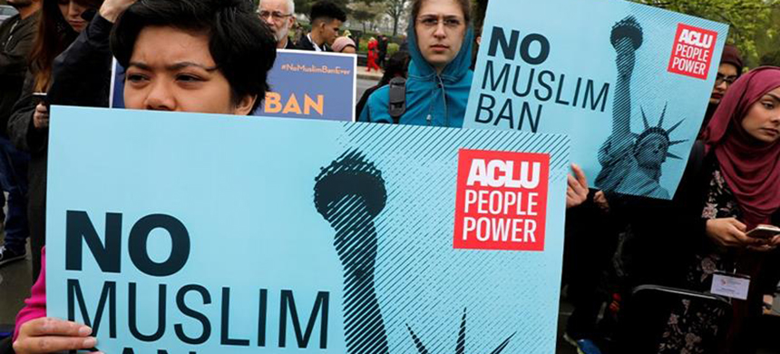 Protesters gathering outside the US Supreme Court, while court justices consider case regarding presidential powers on the legality of President Donald Trump's latest travel ban. (photo: Yuri Gripas/Reuters)