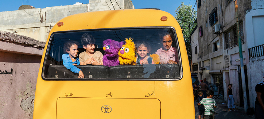 Basma and Jad taking the bus with children in Amman, Jordan. (photo: Ryan Donnell/Sesame Workshop)
