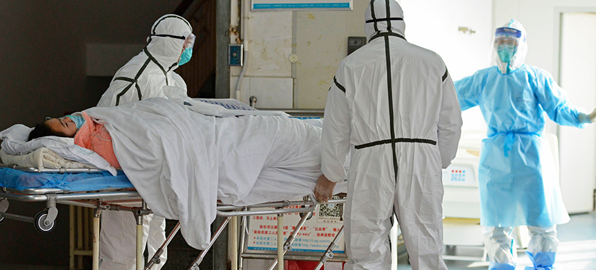 Medical workers transporting a coronavirus patient into an isolation ward in Fuyang, China, on Saturday. Experts fear a coronavirus pandemic, but its severity is uncertain. (photo: Chinatopix/AP)